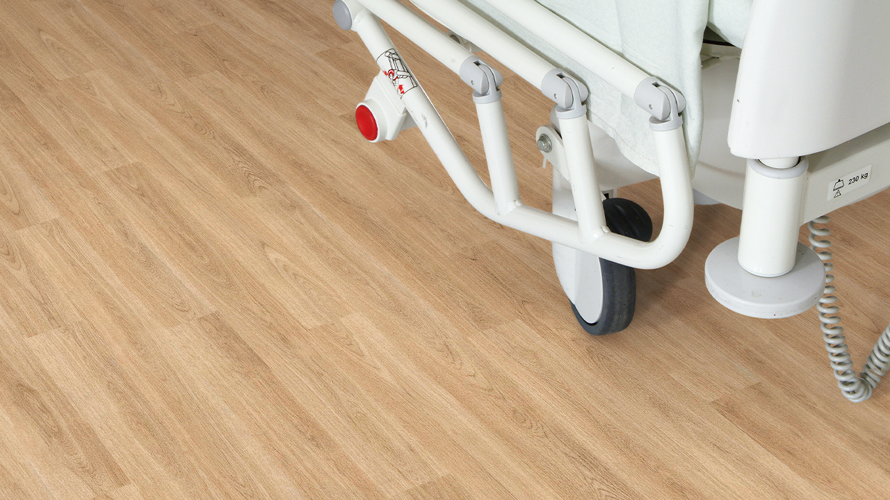 Why is vinyl often the preferred choice for hospital flooring?